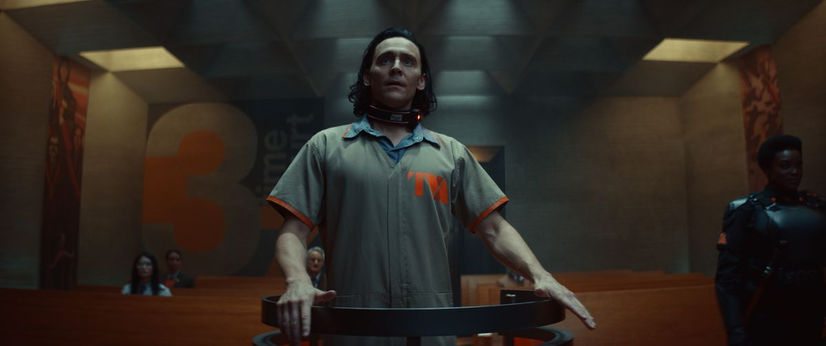 Loki in an unflattering TVA prisoner jumpsuit stands in the dock in Time Court