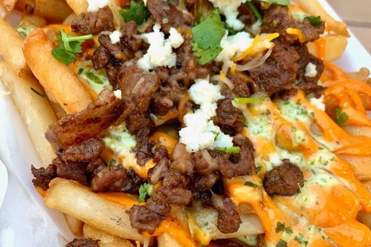 a plate of fries loaded with bulgogi, cheese and other toppings