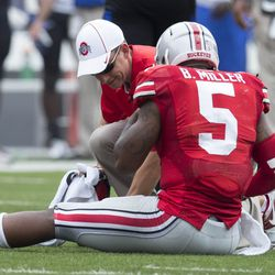 Ohio State Buckeyes quarterback Braxton Miller (5) is treated by a member of the training staff after a play against the Buffalo Bulls at Ohio Stadium. Ohio State won the game 40-20.