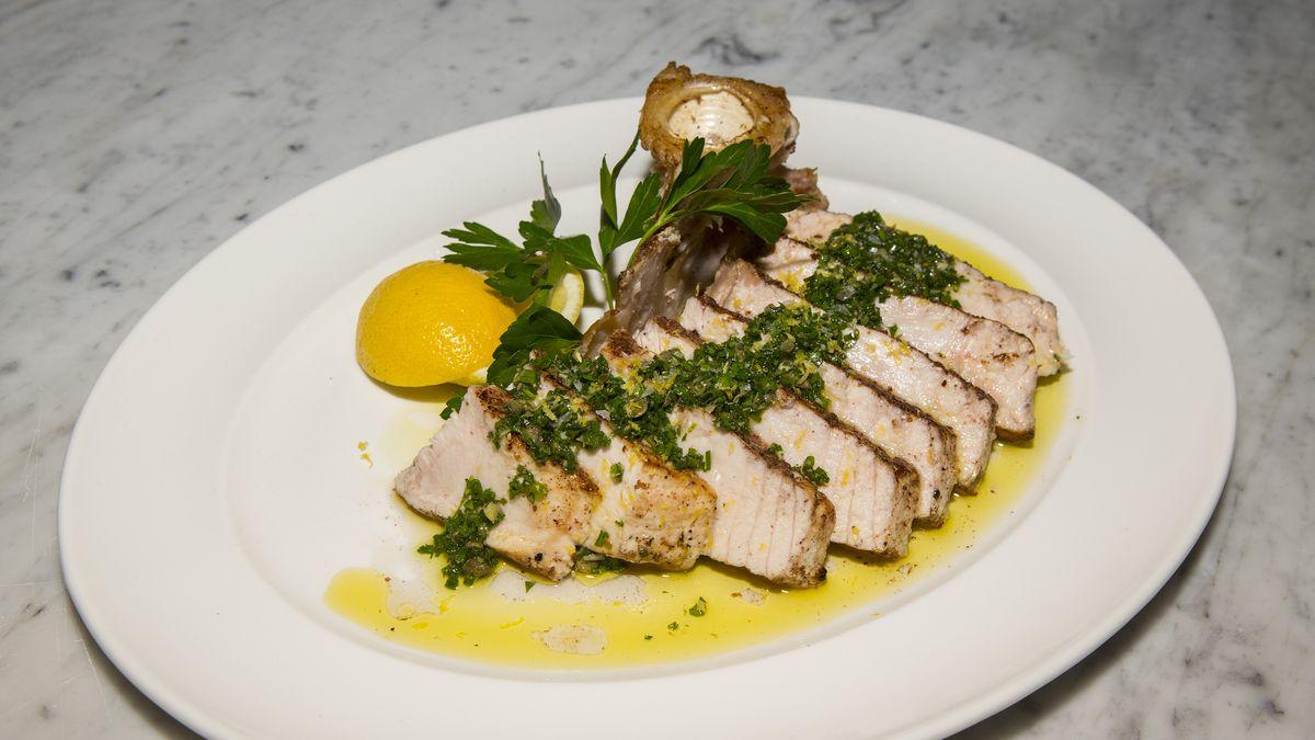 A sliced swordfish steak with lemon wedge