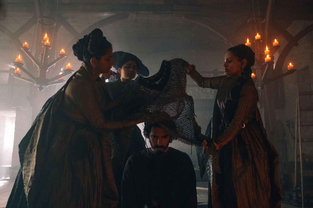 Three women lower a chain shirt over a kneeling Dev Patel in David Lowery's The Green Knight
