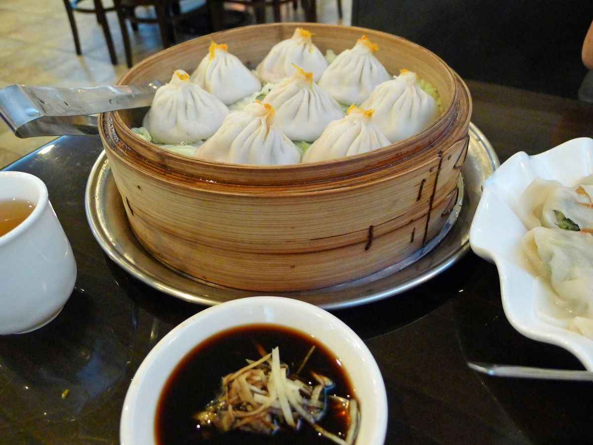 A selection of crab and pork XLB surrounded by other plates and dipping sauces
