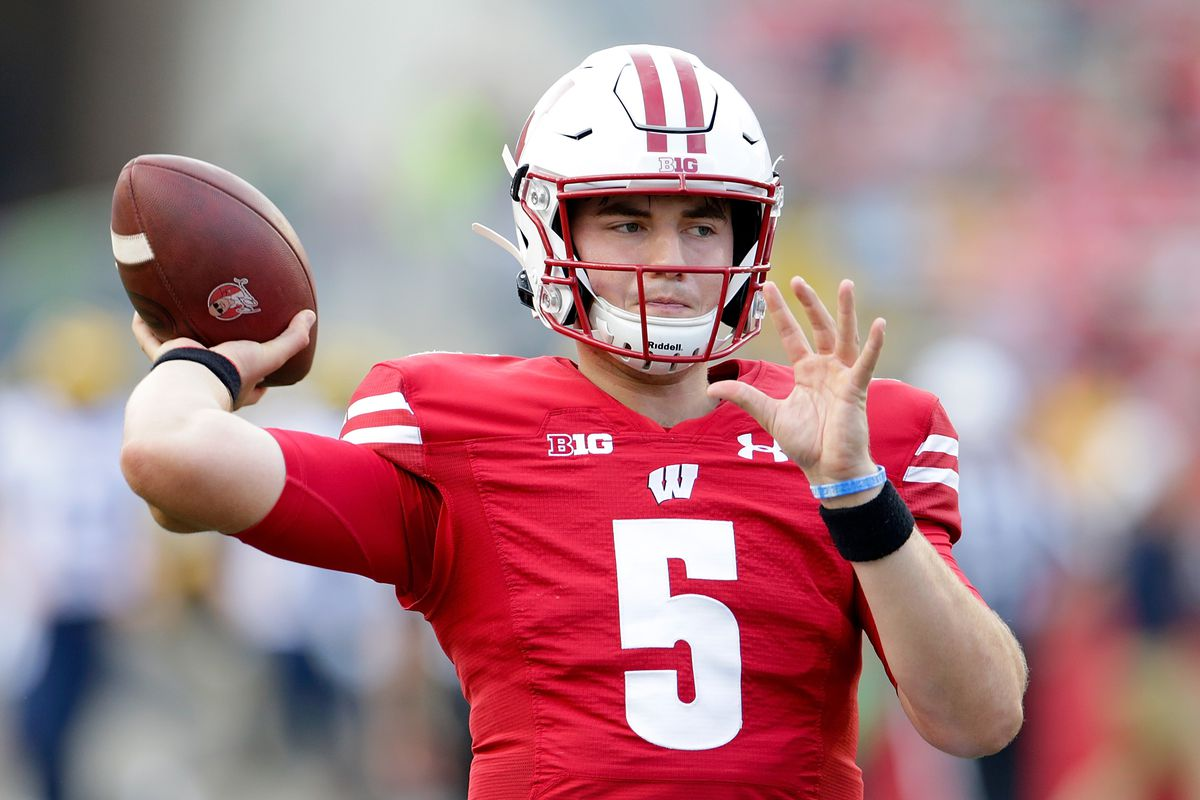 Graham Mertz of the Wisconsin Badgers warms up with a ball honoring Barry Alvarez before the game against the Michigan Wolverines at Camp Randall Stadium on October 02, 2021 in Madison, Wisconsin.