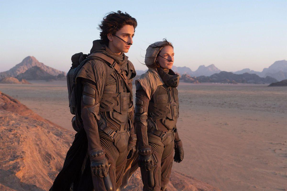 Timothée Chalamet as Paul Atreides and Rebecca Furguson as Lady Jessica Atreides stand in the desert on the set of Denis Villenueve's Dune.
