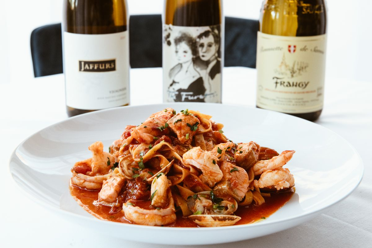 Pasta on a white plate with red sauce and a line of wine bottles in the background.
