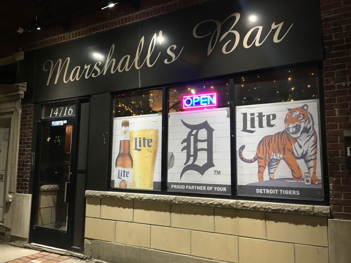 The front of Marshall's Bar at night features signs for Miller Lite and the Detroit Tigers as well as a neon open sign and the sign for the bar written in cursive script.
