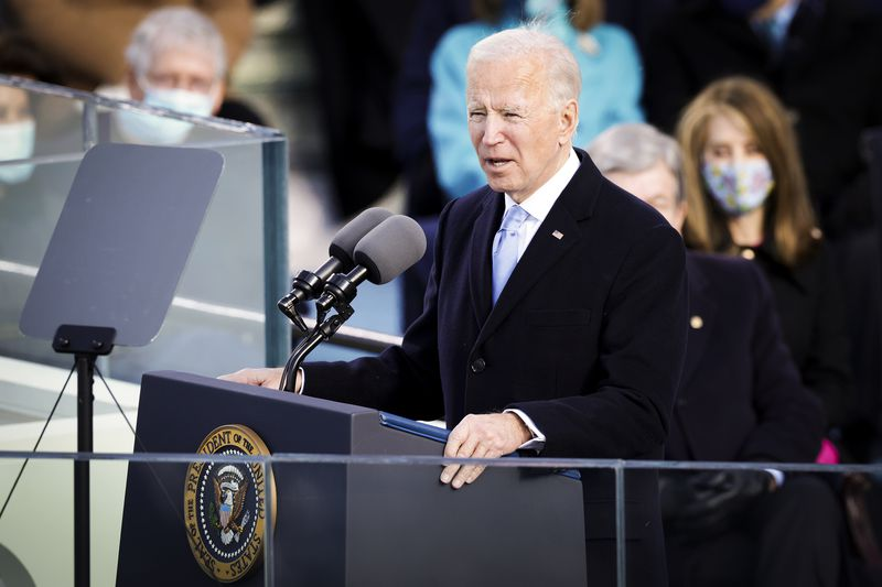 Joe Biden stands at the microphone to deliver his inaugural address.