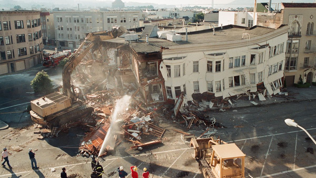 Firefighters spray a three-story building with water as it collapses onto the street.
