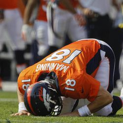 Denver Broncos quarterback Peyton Manning (18) gets up off the turf after taking a hit by the Houston Texans in the second quarter of an NFL football game Sunday, Sept. 23, 2012, in Denver.