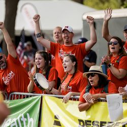 People cheer on runners at the finish line for the Deseret News 5K, 10K, Half Marathon and Marathon at Liberty Park in Salt Lake City on Friday, July 23, 2021.