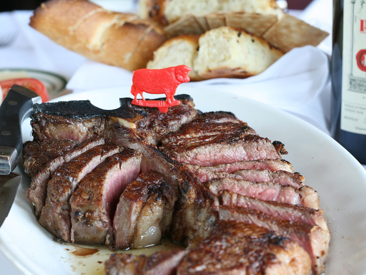 A small red plastic cow is stuck into a porterhouse steak at Wolfgang's Steakhouse