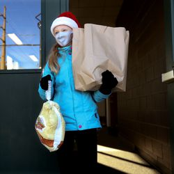 Madelyn Palmer, 11, carries a turkey and a shopping bad full of trimmings at a Crossroads Urban Center food distribution event at Rowland Hall in Salt Lake City on Wednesday, Dec. 23, 2020. This year's Christmas food distribution marks the 23rd year of collaboration with Rowland Hall. Crossroads has been providing social services to individuals and families in need in Salt Lake City and the surrounding areas for over 50 years. Funding and support for the Christmas food distribution came from the staff, students and families of Rowland Hall, the Utah Food Bank, the Eccles Broadcast Center at the University of Utah, the B.W. Bastian Foundation, Rocky Mountain Power, and dozens of other individuals and local religious congregations.