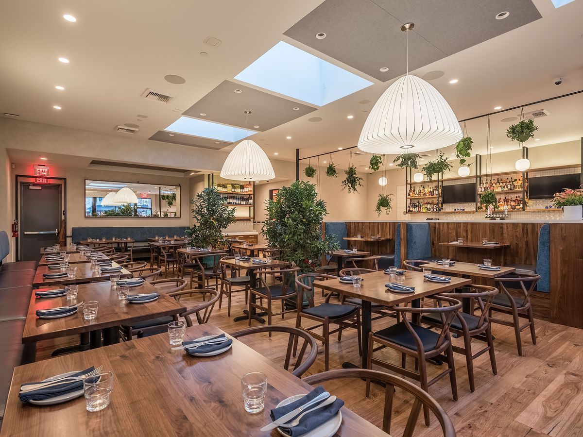 A sunny restaurant set for service, with skylights and tan wooden tables and chairs.