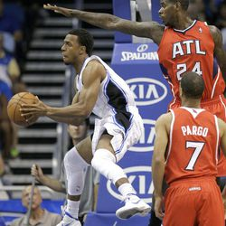 Orlando Magic's Ish Smith passes the ball as he is covered by Atlanta Hawks' Marvin Williams (24) and Atlanta Hawks' Jannero Pargo (7) during the first half of an NBA basketball game on Friday, April 13, 2012, in Orlando, Fla.