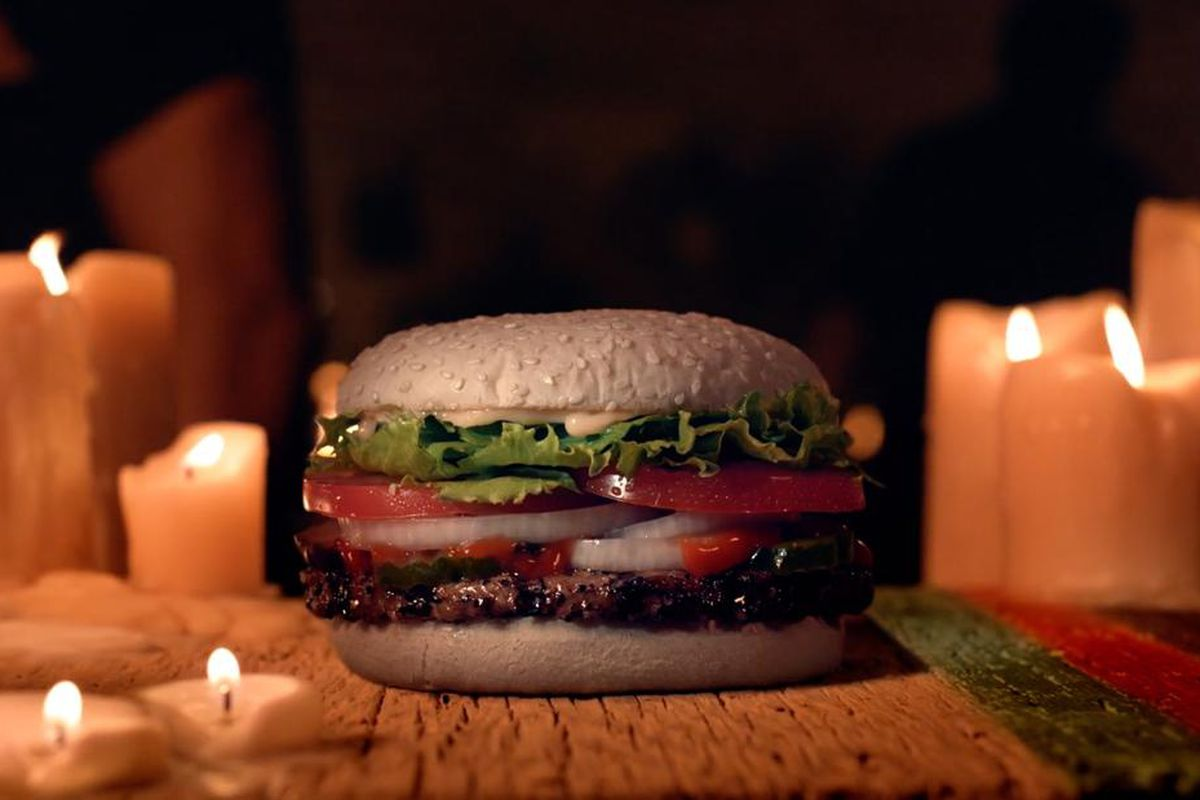 A burger with lettuce and tomato and a seeded bun surrounded by candles