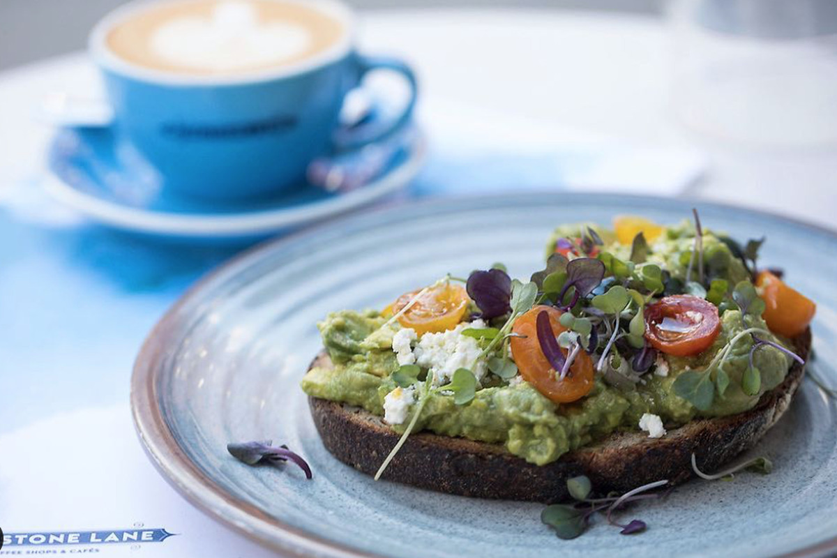 Avocado toast on a plate with a blue coffee mug in the rear