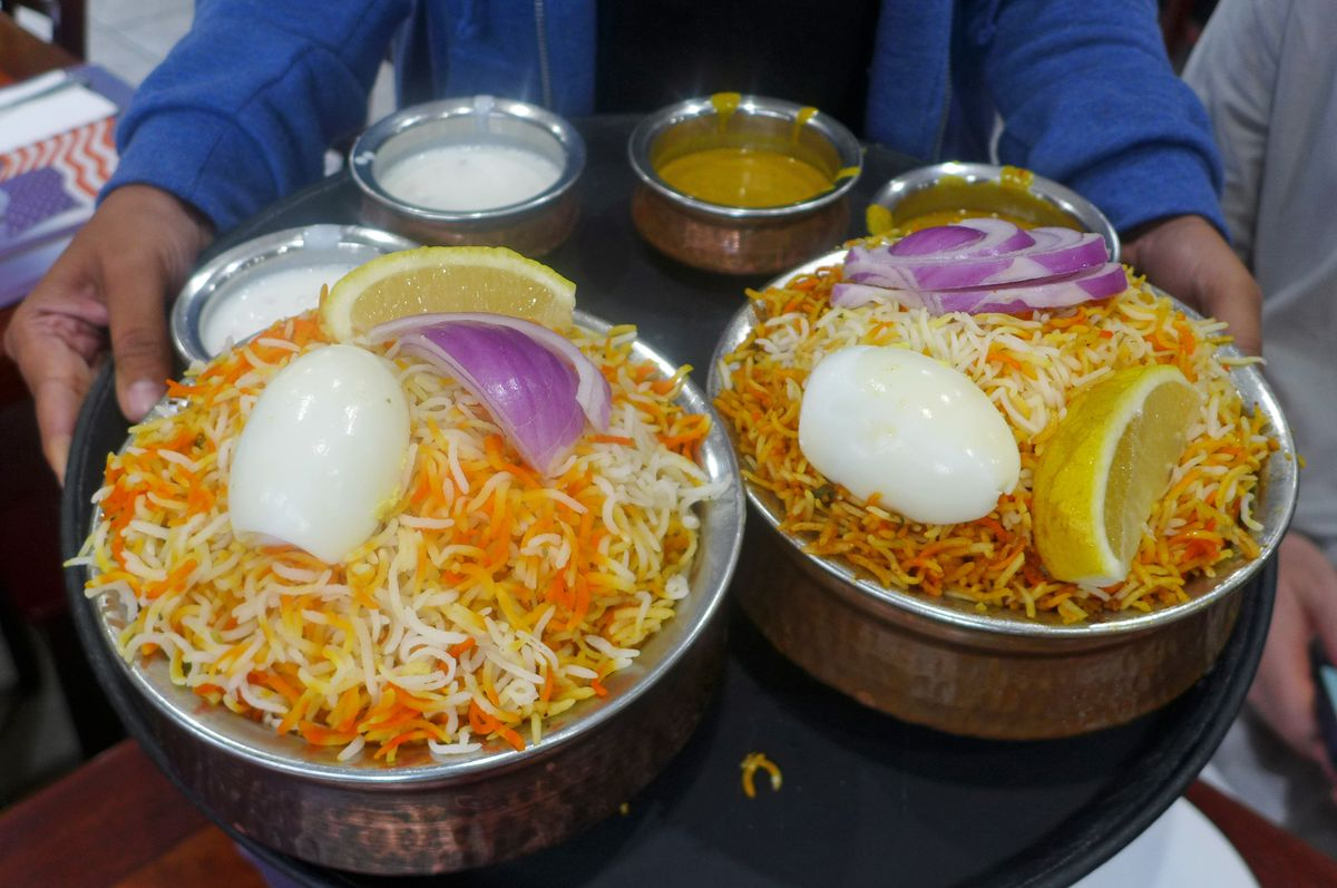 Two serving bowls of biryani with colorful rice and a boiled egg on top, the rice on the right is darker.