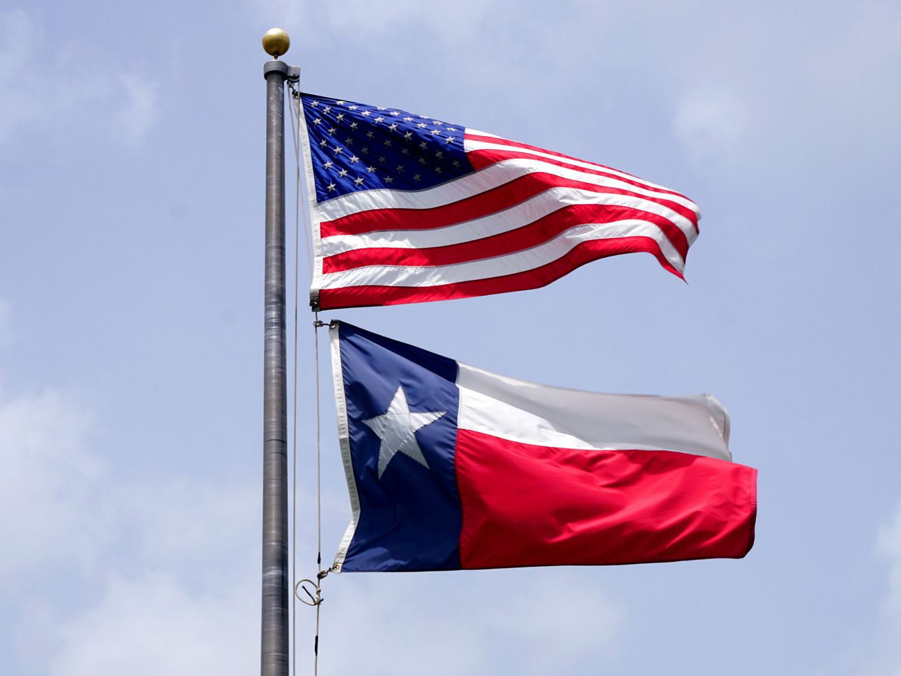 The state flag of Texas is shown beneath the flag of the United States.