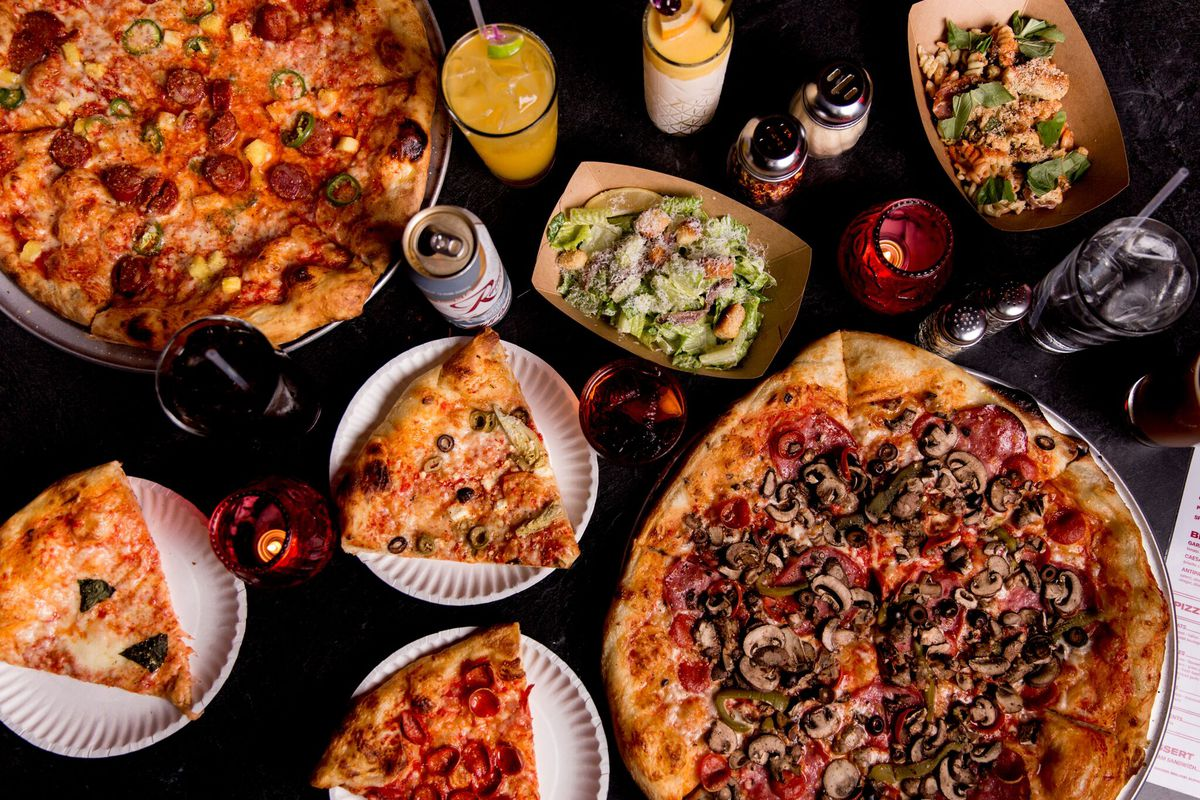 A top-down view of several different pizzas, with a variety of toppings, alongside cocktails, beers, and salads.