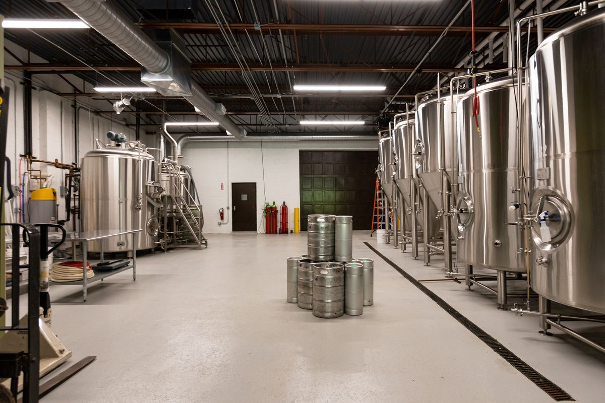 Silver brewing tanks line the walls in the production room.