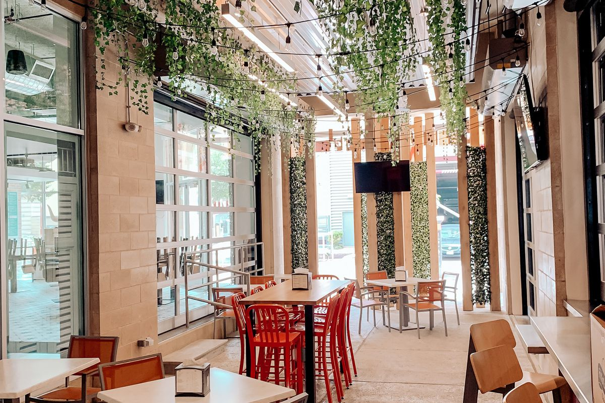 an indoor/outdoor dining space with lots of windows and vines hanging form the cieling