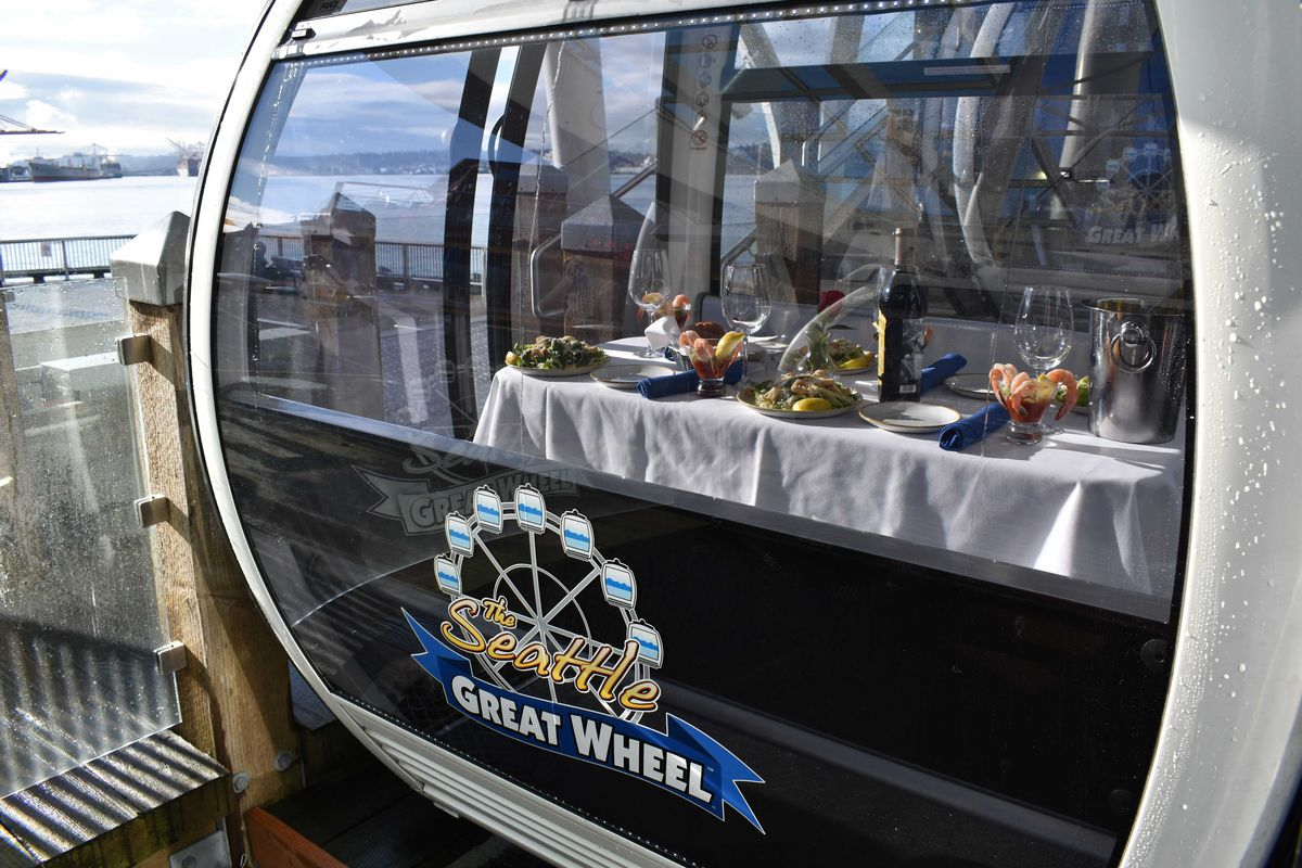 A table set inside a gondola at Seattle's Great Wheel, with a view of the Puget Sound in the background on a cloudy day