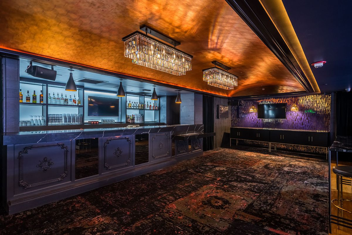 A dark carpet, chandelier, and marble bar inside a venue.