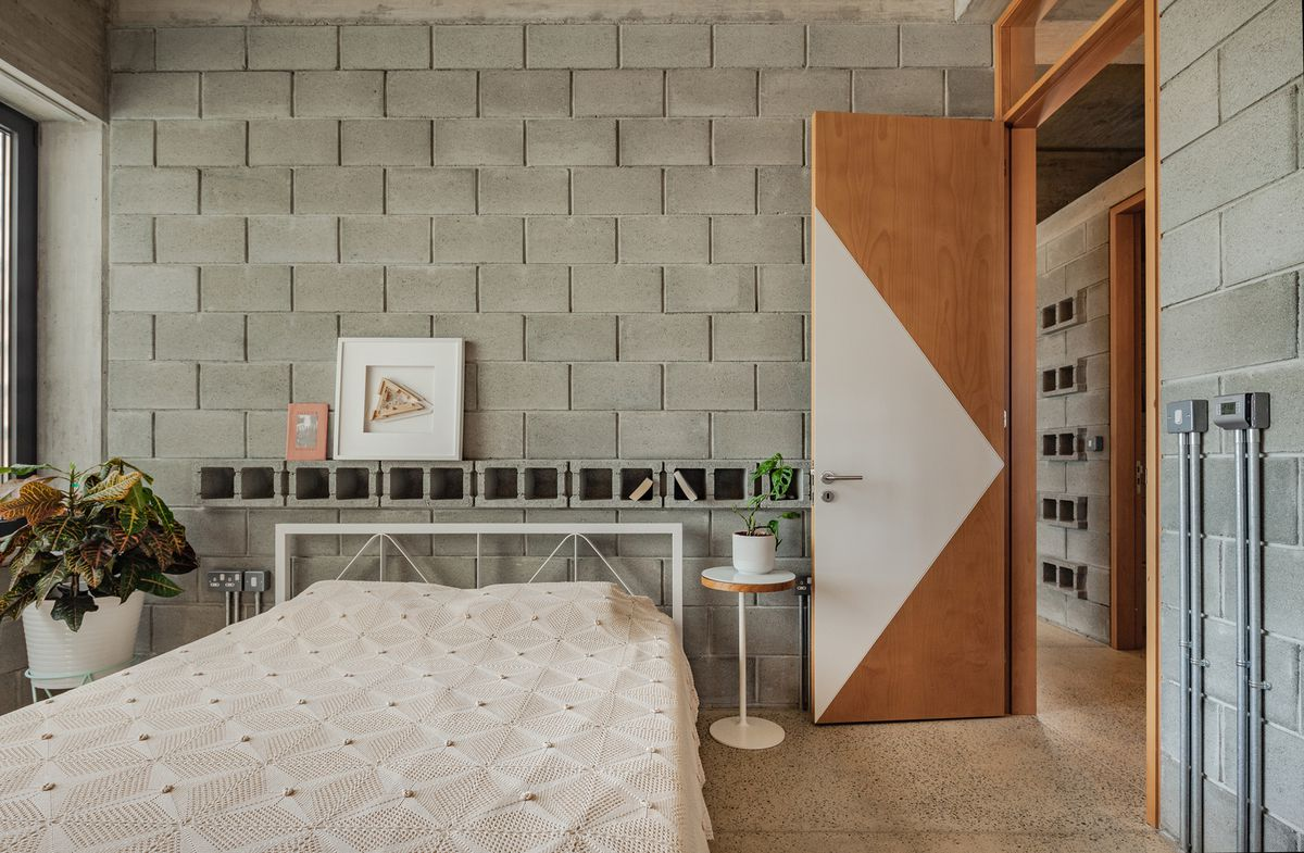 Bedroom featuring concrete masonry unit walls.