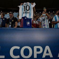 Fans show off a Messi shirt