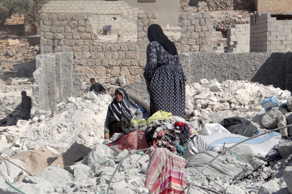 Syrian women collect their possessions after US-led coalition airstrikes on ISIS positions near Idlib, Syria.