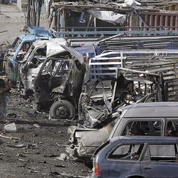 British soldiers gather evidence next to destroyed cars at the scene of a suicide car bomb attack on the outskirts of Kabul Tuesday. A Taliban suicide bomber attacked a NATO convoy, killing at least seven people and wounding more than 50, officials said, just days before the presidential election that the militant group has vowed to disrupt.