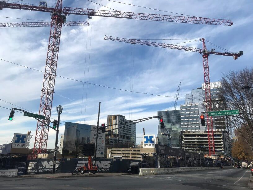 A series of cranes in the air above a contruction site.