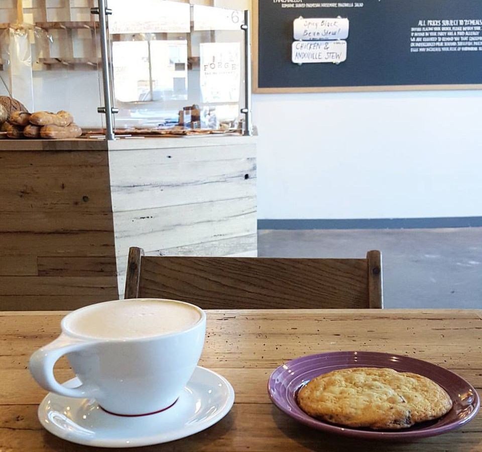 A white mug of hot chocolate and a small maroon plate with a cookie on it sit on a light wooden table. A chalkboard and a pastry display case of a cafe are visible in the background.