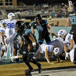 Coastal Carolina's Reese White, center, scores a touchdown during the first half of an NCAA college football game against BYU Saturday, Dec. 5, 2020, in Conway, S.C.
