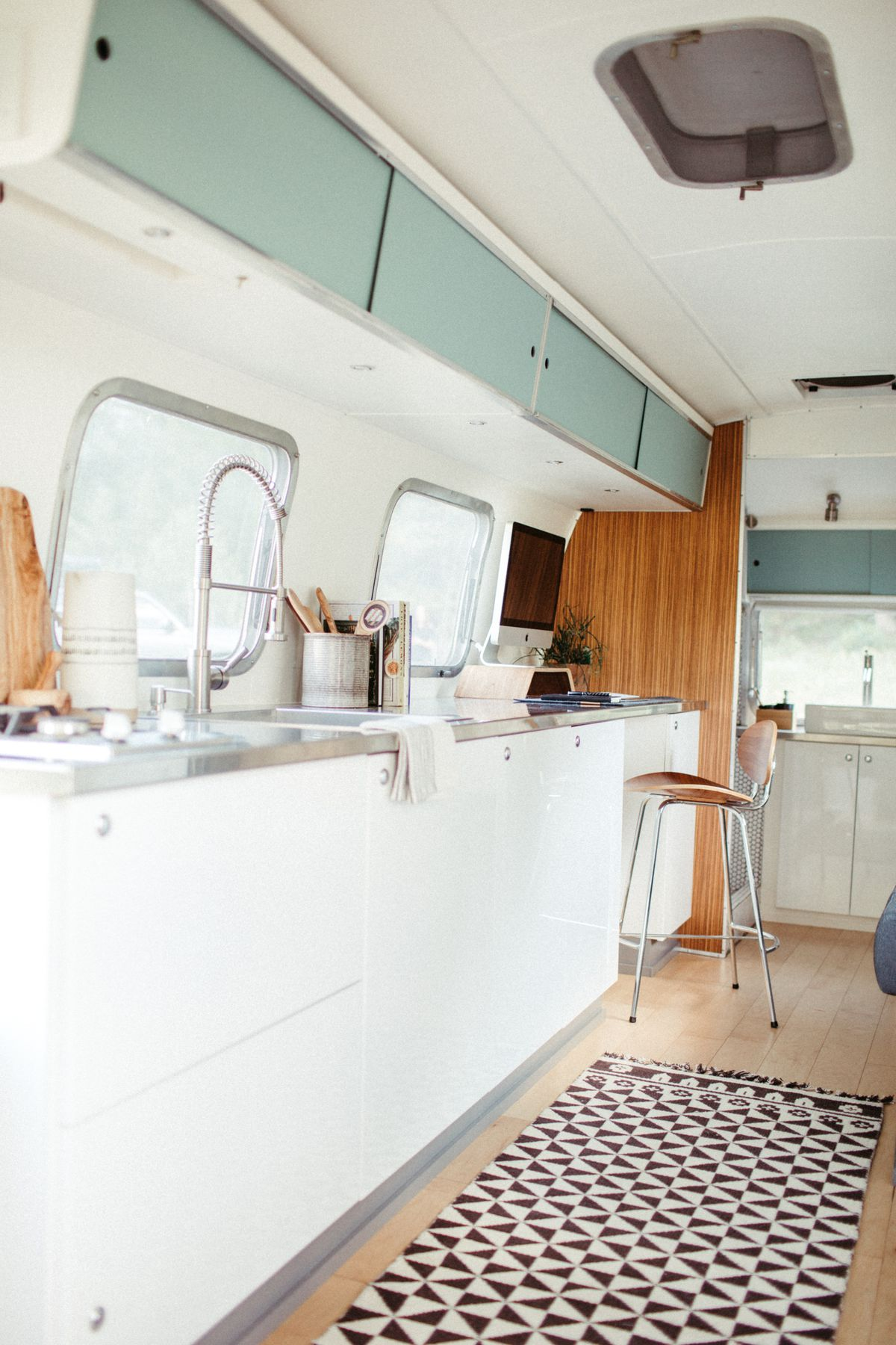 A look at the kitchen area inside a travel trailer, with white cabinets and stainless steel counters.
