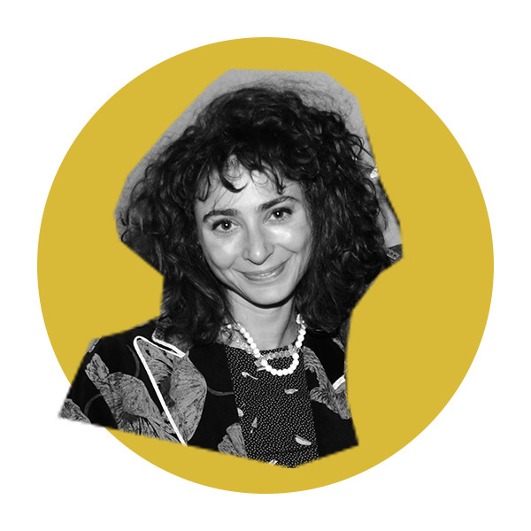 A black and white photo of Alexi Pappas with curly shoulder length hair, wearing a floral-printed shirt and beaded necklace.