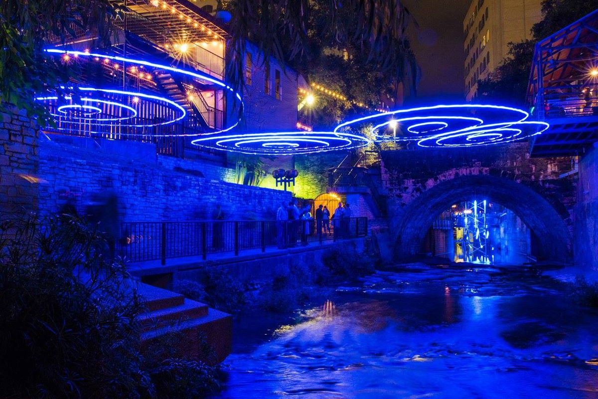 A blue light sculpture underneath a tunnel over a creek at night
