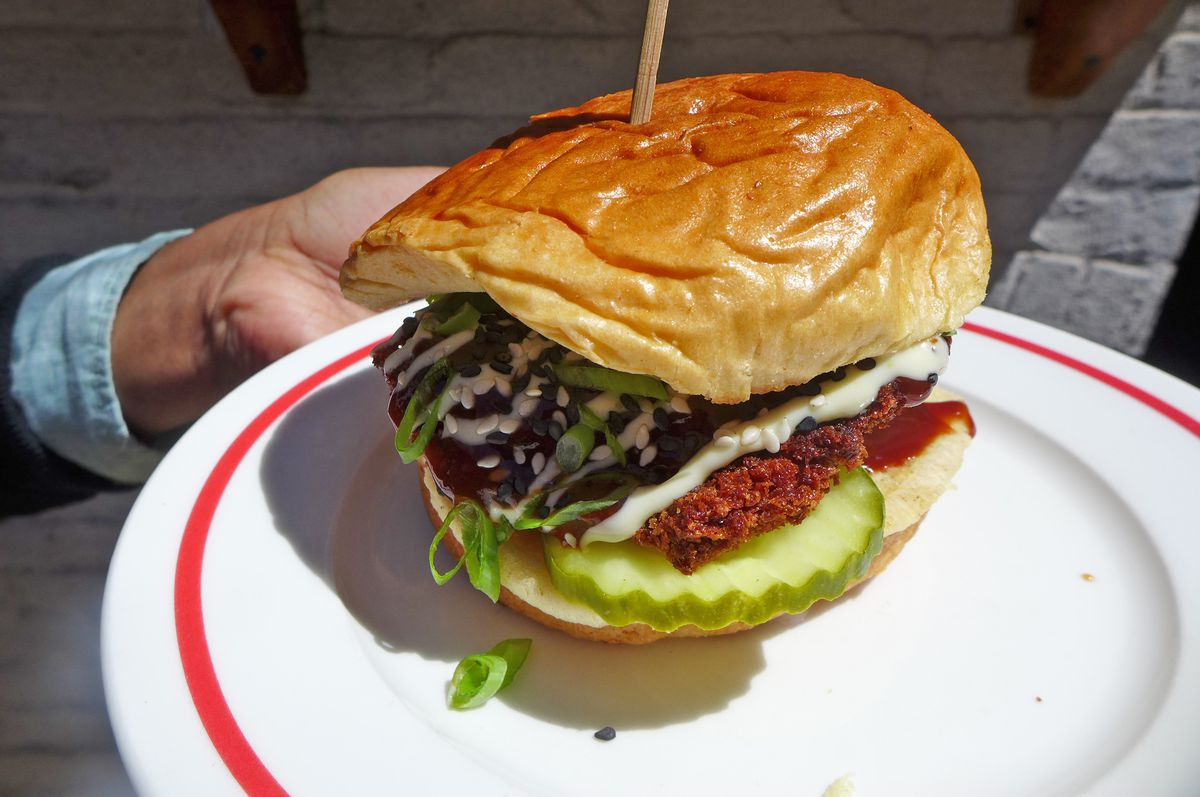 A brioche bun with dark fried chicken topped with white sauce.