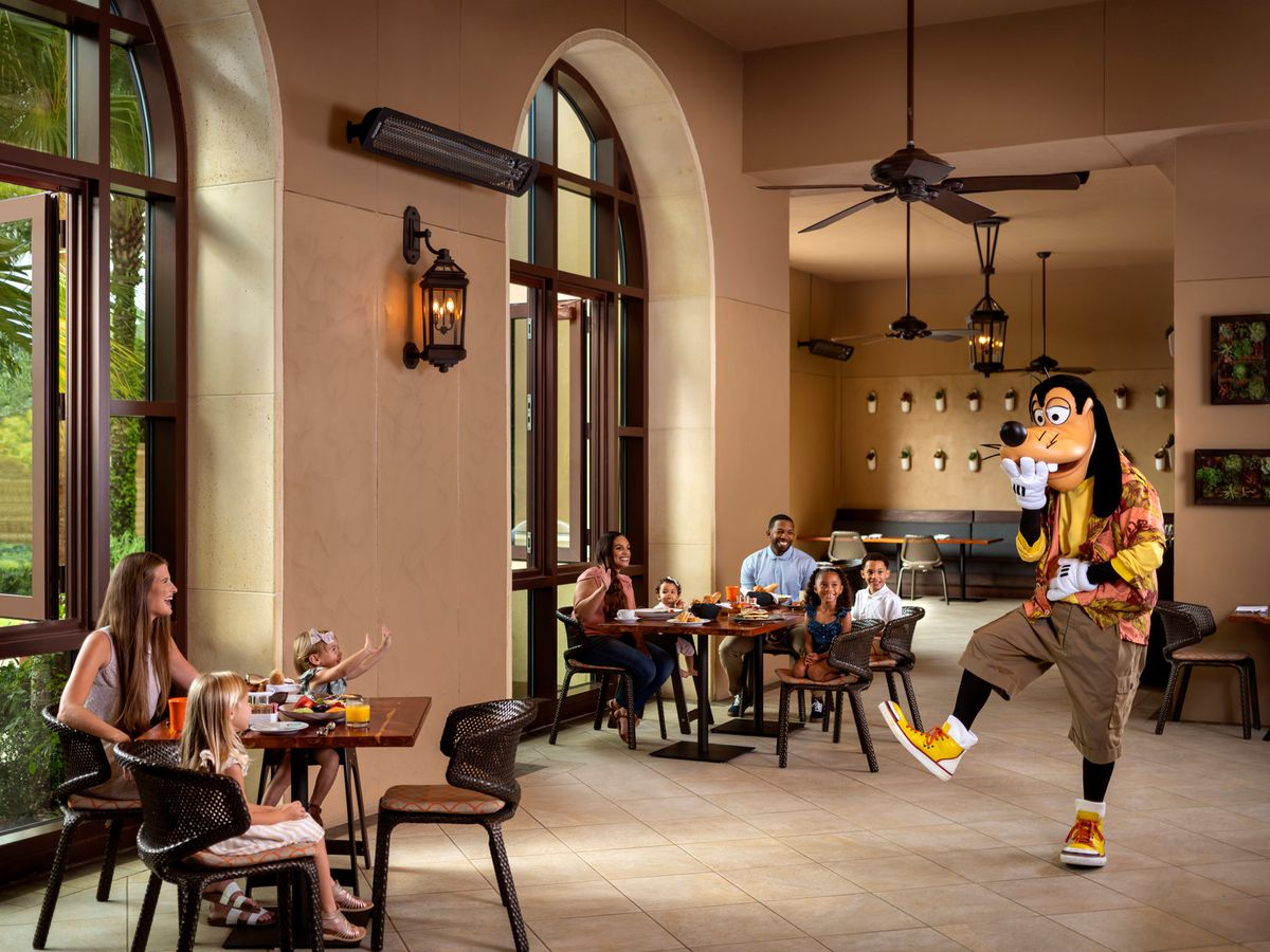 A costumed Goofy laughs as he approaches a table of children and their mother
