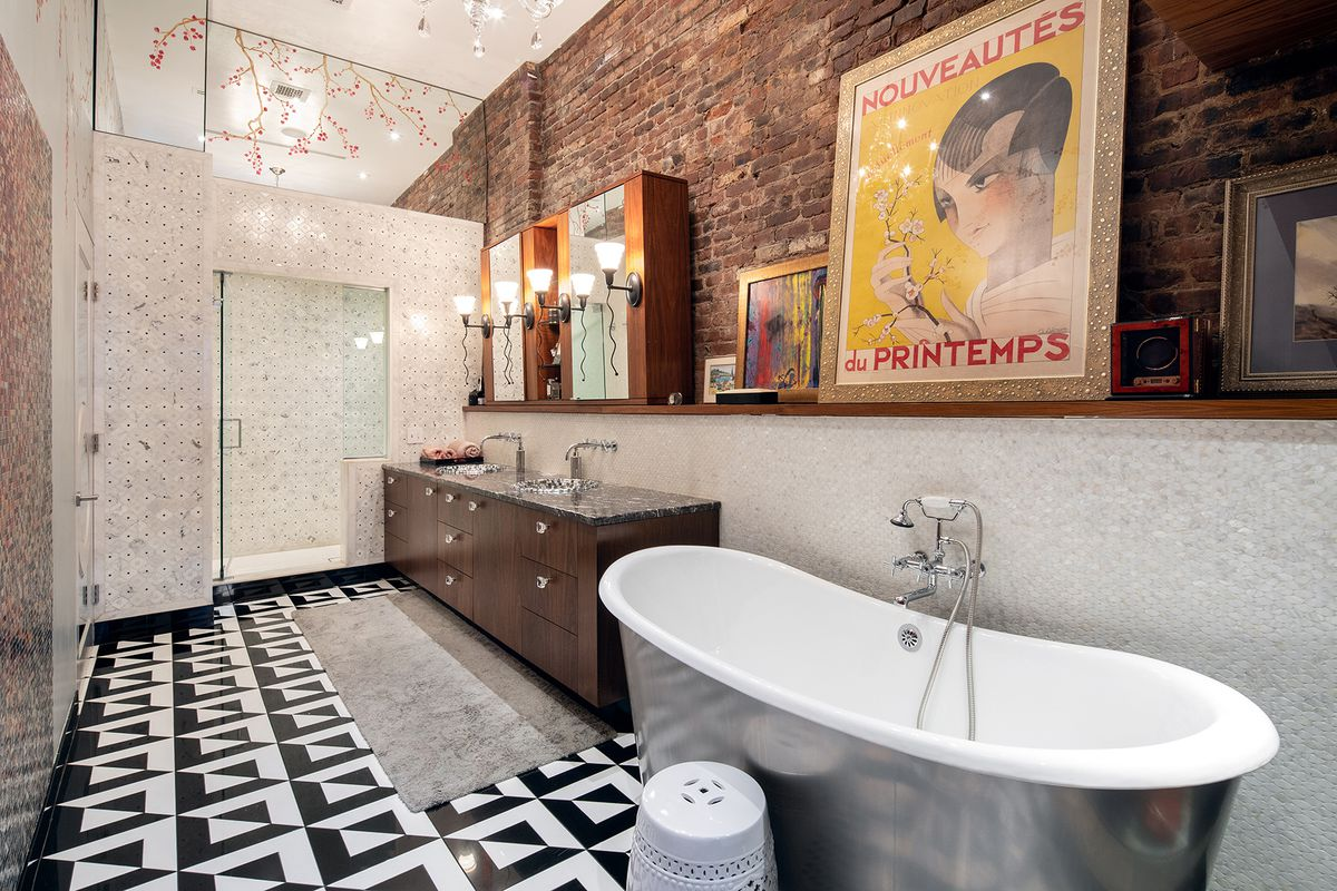 A bathroom with black and white floor tiles, mother of pearl walls, and several framed paintings and posters on a stand.
