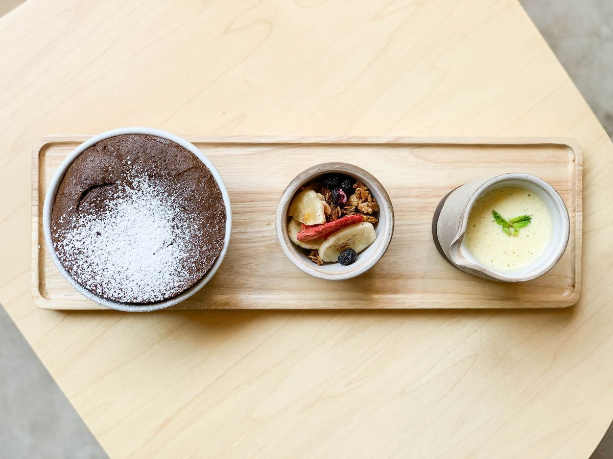 A rectangle tray with chocolate souffle and granola.