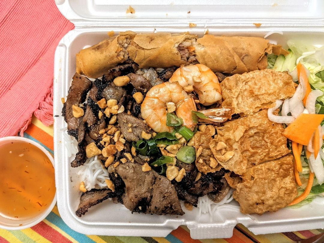 Overhead view of a white styrofoam container stuffed with a Vietnamese dish: grilled shrimp, pork, and bean curd over tofu, topped with peanuts and herbs. It's sitting on a tablecloth with pink, orange, yellow, blue, and green stripes.
