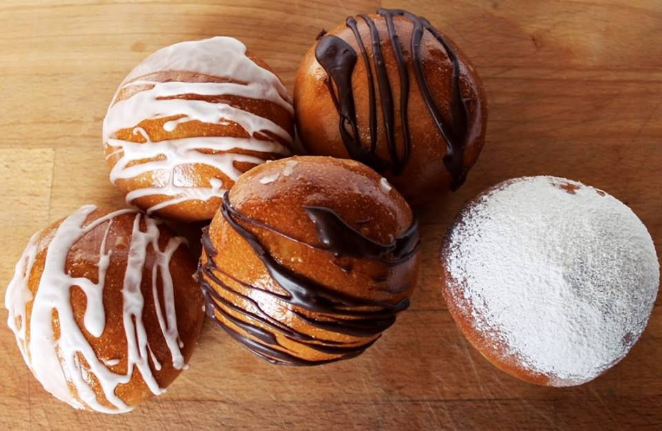 A pile of baked paczki drizzled with icing and powdered sugar.
