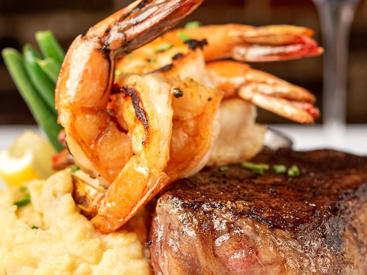 Four prawns, with tails on, rest above a prime filet upon a bed of mashed potatoes.