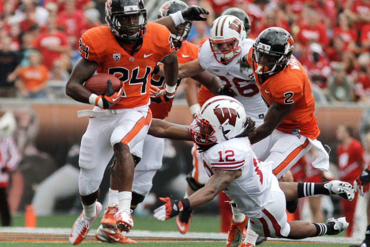 Sept. 8, 2012; Corvallis, OR, USA; Oregon State Beavers tailback Storm Woods (24) is tripped up by Wisconsin Badgers free safety Dezmen Southward (12) during the second half at Reser Stadium. Mandatory Credit: Jaime Valdez-US PRESSWIRE