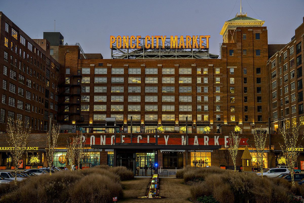 A massive brick building called Ponce City Market is shown with Christmas lights all around it.