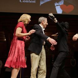 """2007 Nobel Prize laureate in Economics Eric Maskin, center, embraces a woman after a drawing for a """"Win a Date with a Nobel Laureate"""" contest during a performance at the Ig Nobel Prize ceremony at Harvard University, in Cambridge, Mass., Thursday, Sept. 20, 2012. The Ig Nobel prize is an award handed out by the Annals of Improbable Research magazine for silly sounding scientific discoveries that often have surprisingly practical applications."""