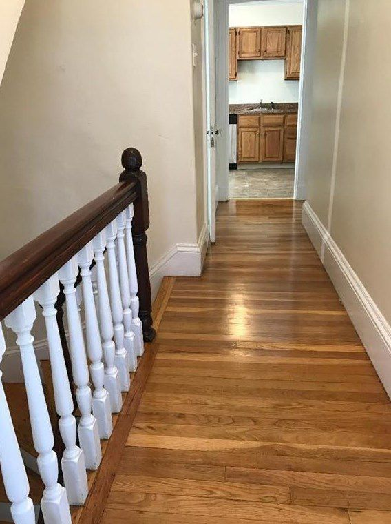A narrow hallway at the top of some stairs and leading to a kitchen.