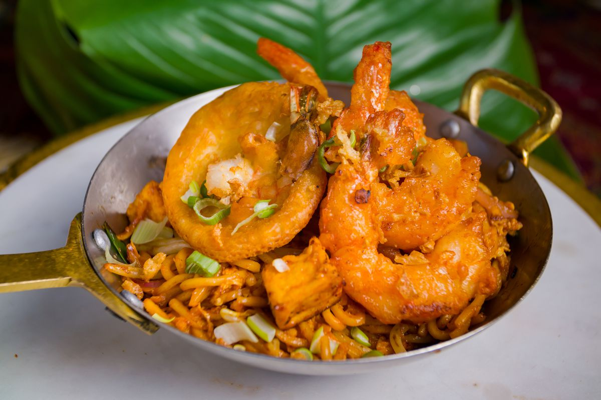 A yellowish rice dish with giant pieces of shrimp peeking out all placed in a gold-rimmed vessel