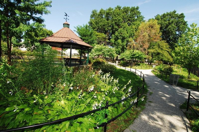 A park. There is a path surrounded by plants. The path leads to a large gazebo with a brown roof and seating area.